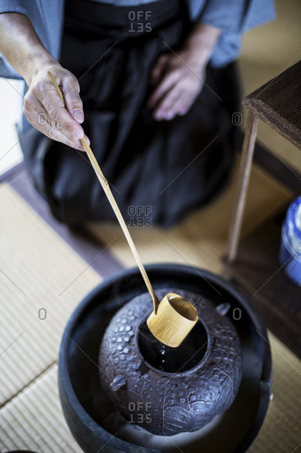 High angle close up of traditional Japanese Tea Ceremony, man using a Hishaku, a bamboo ladle, to pour hot water.
