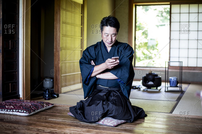 Japanese man wearing kimono sitting on floor in traditional Japanese house, using mobile phone.