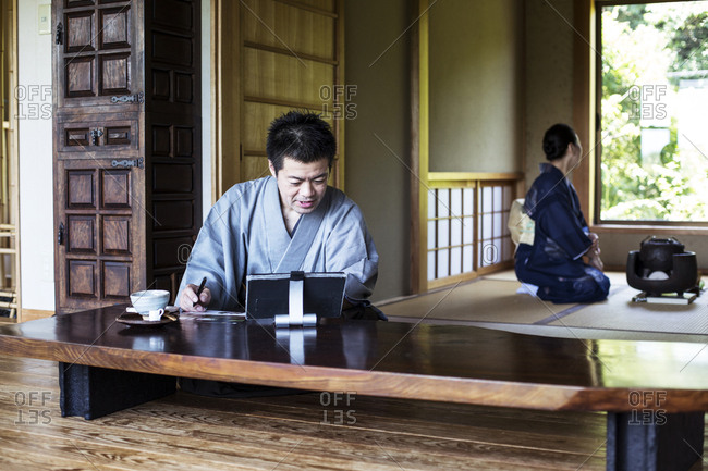 Japanese man wearing kimono sitting on floor in traditional Japanese house, looking at digital tablet.