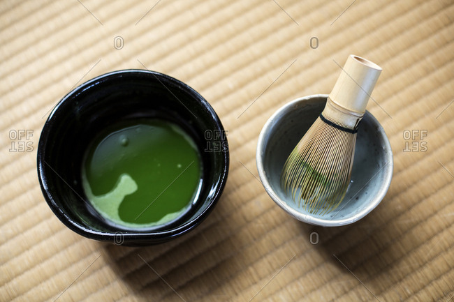 Tea ceremony utensils including bowl of green Matcha tea and bamboo whisk.