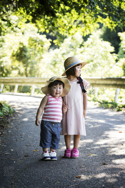 Two Japanese girls wearing sun hats standing on path, holding hands.