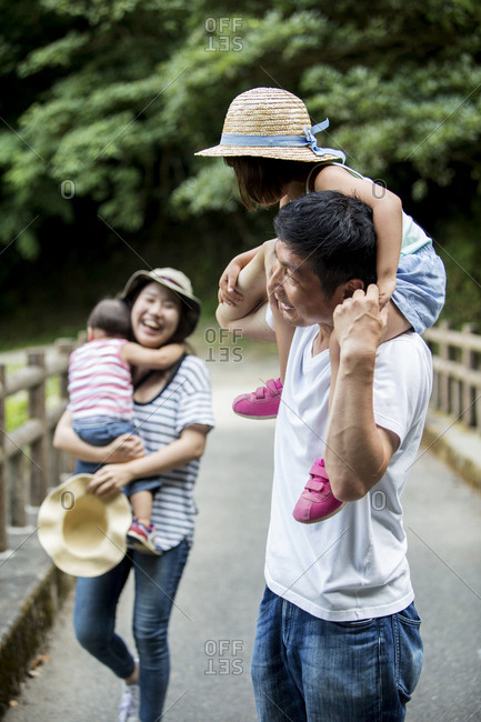 Japanese girl, smiling woman holding hat and man carrying toddler on his shoulders standing on wooden bridge.