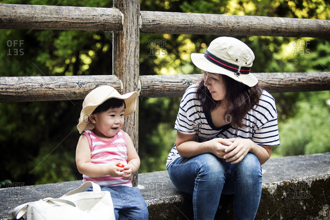 Smiling Japanese woman sitting next to little girl wearing sun hat, striped top and jeans.