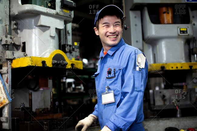 Japanese man wearing baseball cap and blue overall standing in factory, smiling.