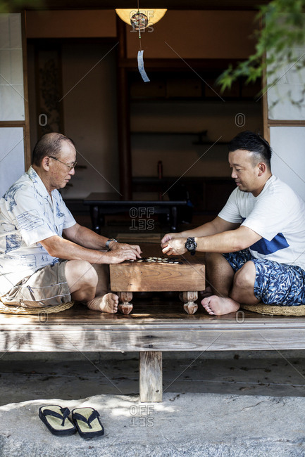 Two Japanese men sitting on floor on porch of traditional Japanese house, playing Go.