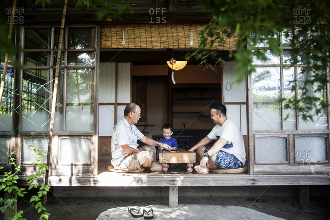 Two Japanese men and little boy sitting on floor on porch of traditional Japanese house, playing Go.