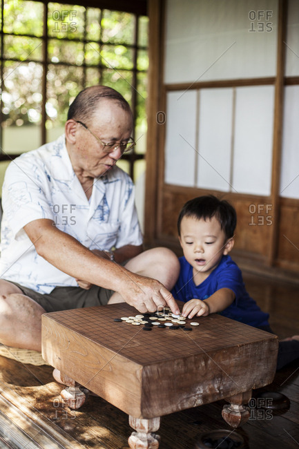 Japanese man and little boy sitting on floor on porch of traditional Japanese house, playing Go.