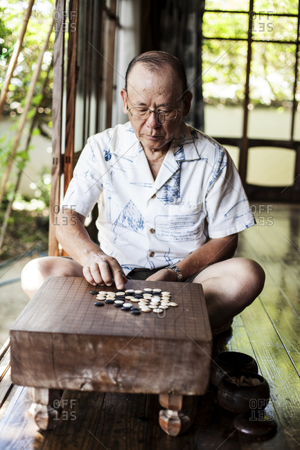 Japanese man sitting on floor on porch of traditional Japanese house, playing Go.