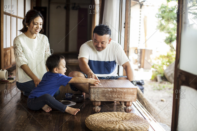 Japanese woman, man and little boy sitting on floor on porch of traditional Japanese house, playing Go.