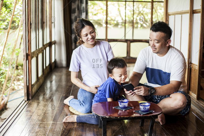 Japanese woman, man and little boy sitting on floor on porch of traditional Japanese house, drinking tea.