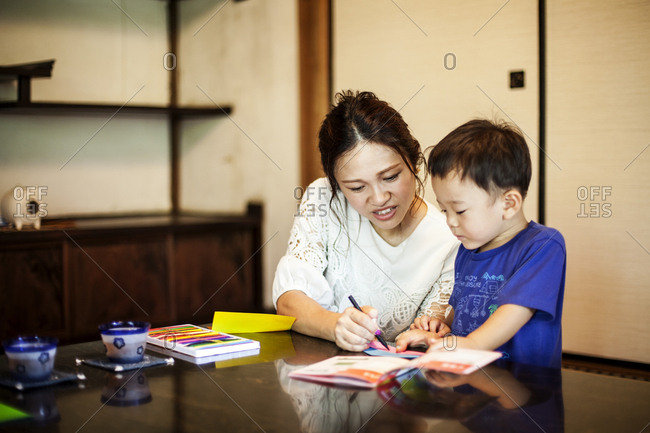 Japanese woman and little boy sitting at a table, drawing with colouring pens.