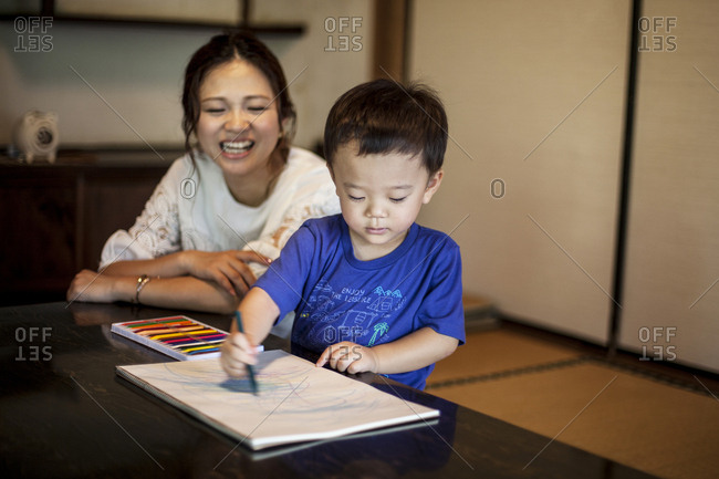 Smiling Japanese woman and little boy sitting at a table, drawing on white paper with colouring pens.