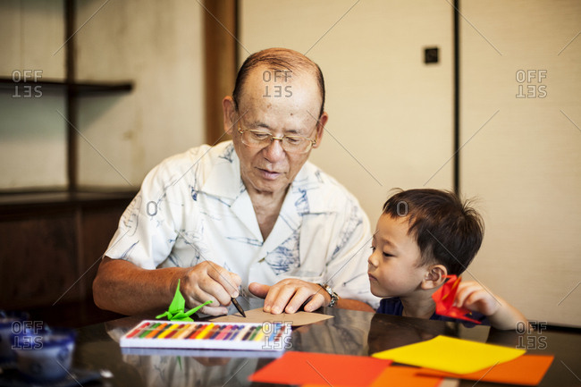 Japanese man and little boy sitting at a table, making Origami animals using brightly coloured paper.
