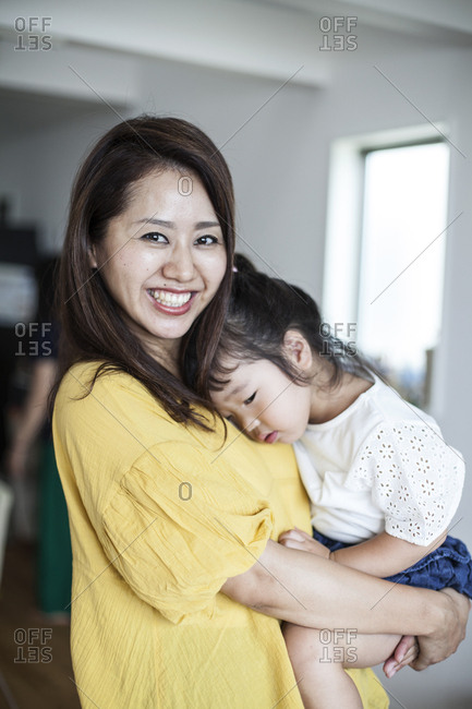 Portrait of Japanese woman standing in a living room carrying young girl, smiling at camera.