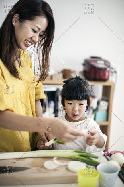 Japanese woman and young girl standing at a kitchen table, cutting leeks.
