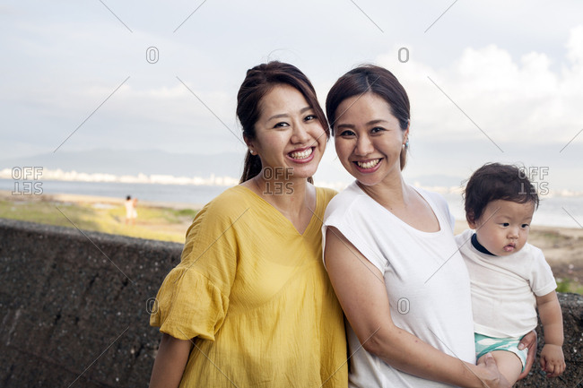 Portrait of two Japanese women, one carrying a toddler, standing on promenade by ocean, smiling at camera.