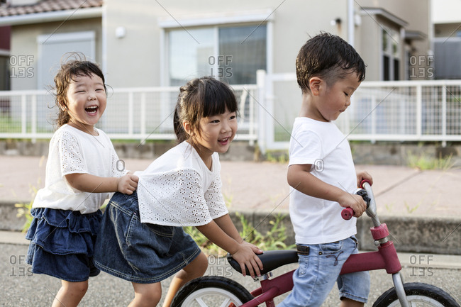 Portrait of two Japanese girls and boy playing on street with a bicycle, smiling at camera.