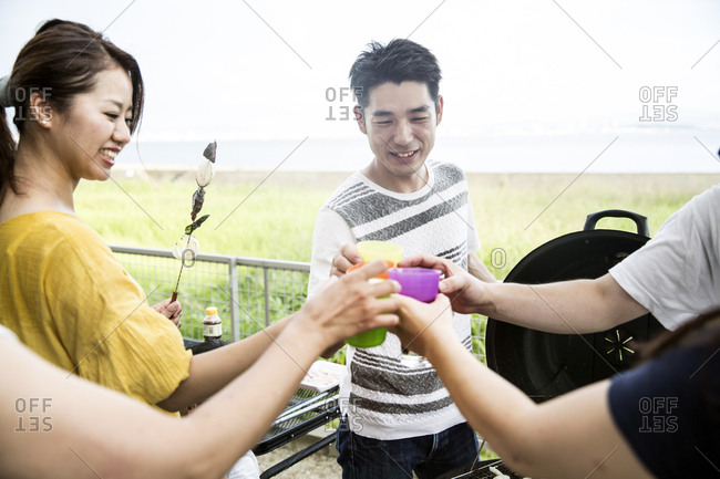 Group of Japanese men and women standing outdoors, toasting with plastic beakers.