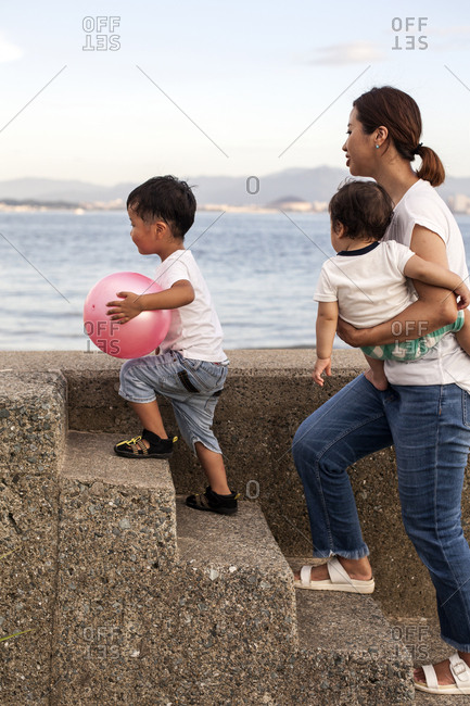 Japanese woman carrying toddler and young boy with pink ball walking up concrete steps by the ocean.
