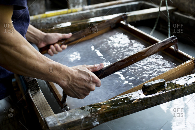 Japanese man in a workshop, holding a wooden frame with pressed pulp, making traditional Washi paper.