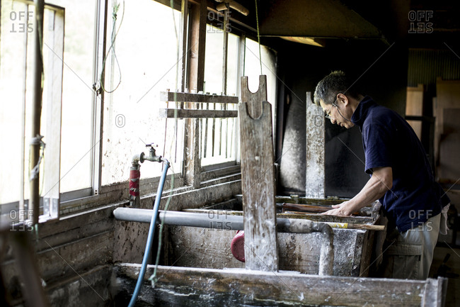 Japanese man in a workshop leaning over a vat of liquid, the traditional Washi papermaking process.