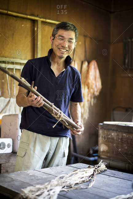 Japanese man standing in a traditional Washi workshop, holding a bunch of mulberry twigs, plant fibre ingredients and strips of fibre on a table.