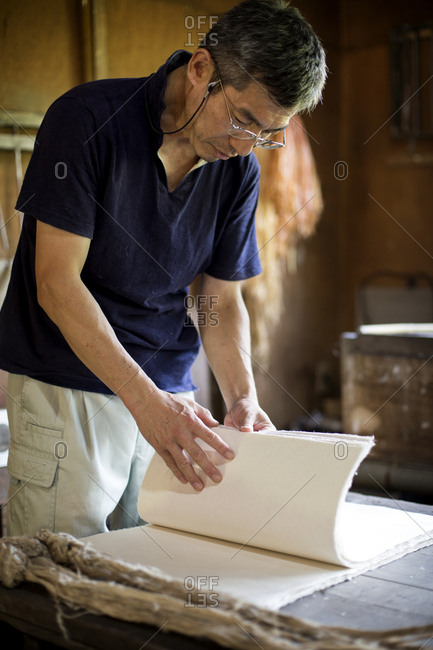 Japanese man standing in a workshop,  checking through sheets of traditional Washi paper.