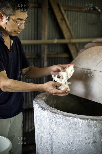 A man separating pieces of vegetable fibres above a vat, ingredient of traditional Washi paper.
