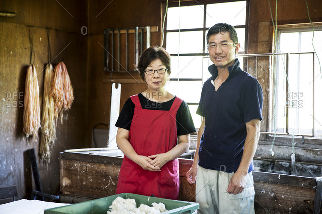 Japanese woman and man standing in a Washi workshop by a vat of pulp, basic plant based ingredients for making paper.