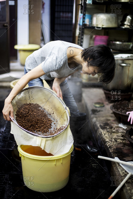 Japanese woman standing in a textile plant dye workshop, pouring plant dye from a sieve into a yellow bucket..