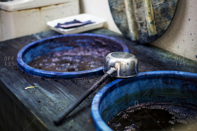 High angle close up of ladle and buckets with blue dye in a textile plant dye workshop.
