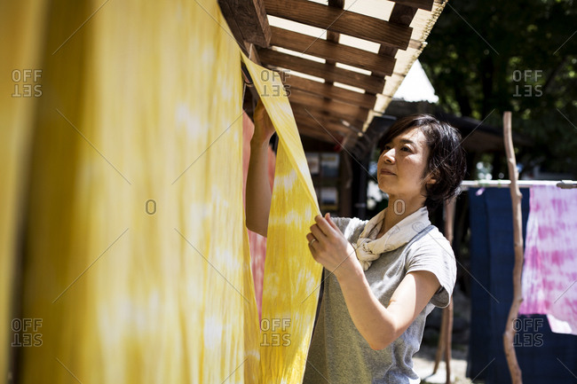 Japanese woman standing in a textile plant dye workshop, hanging up freshly dyed bright yellow fabric.