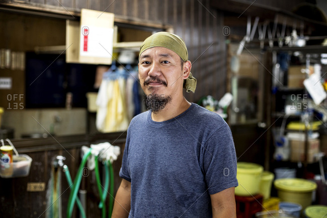Japanese man wearing bandana in a textile dyeing workshop, smiling at camera.