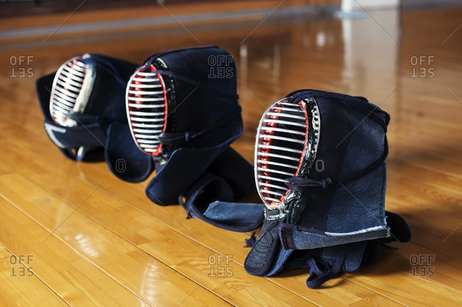 High angle close up of row of three Kendo masks on hardwood floor.