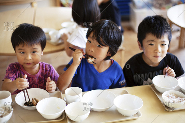 High angle view of three boys sitting at a table in a Japanese preschool, eating with chopsticks.