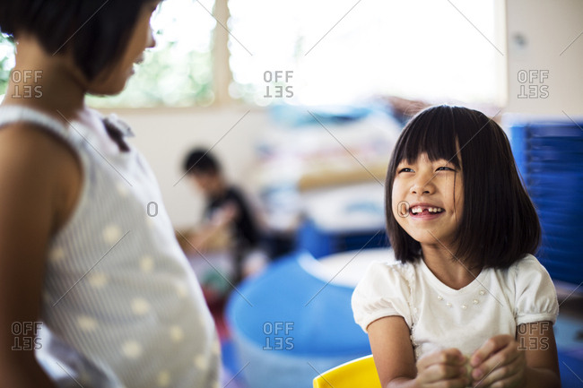 Two smiling girls in a classroom in a Japanese preschool.