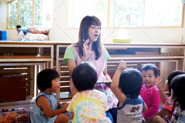 Female teacher telling story to group of children in a Japanese preschool.