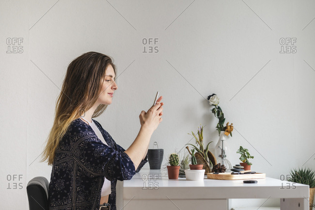 Young woman using cell phone at home surrounded by plants