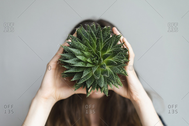 Woman holding plant in front of her face