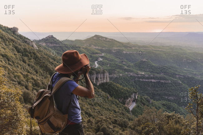 Spain- Barcelona- Montserrat- man with backpack taking photo of view at sunset