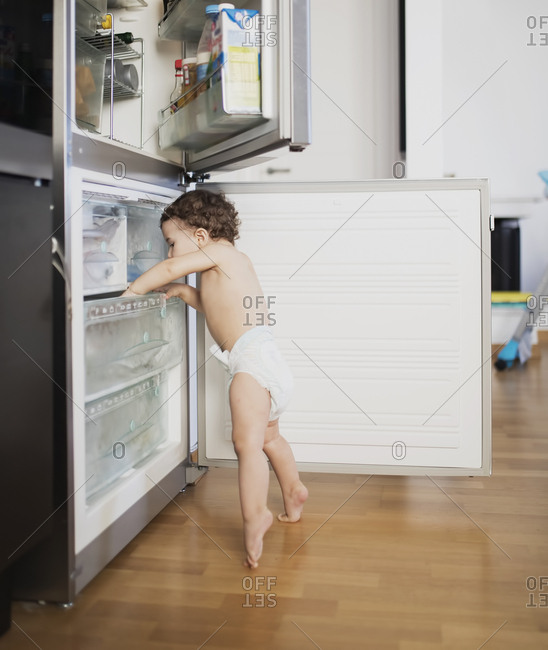 Baby boy wearing diaper exploring refrigerator in the kitchen