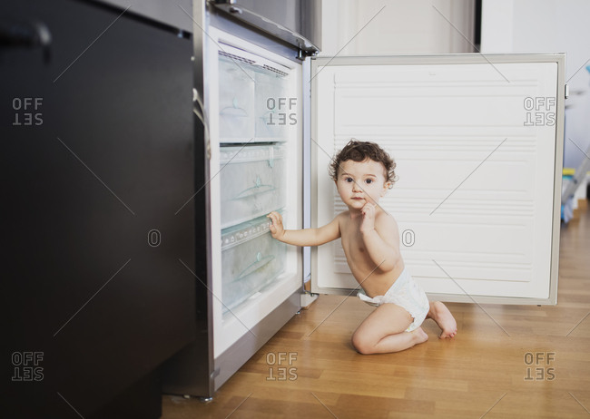 Portrait of baby boy wearing diaper crouching in front of refrigerator in the kitchen