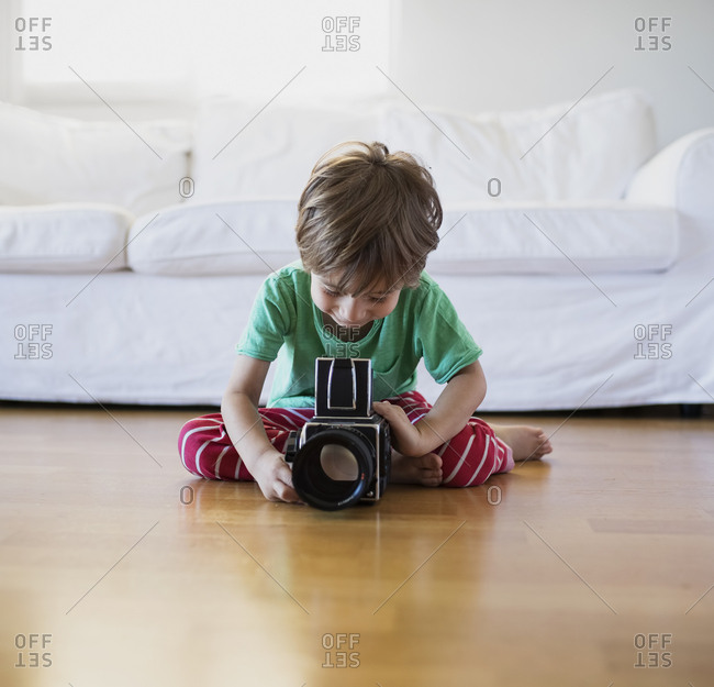 Toddler boy sitting on the floor at home using an old-fashioned film camera