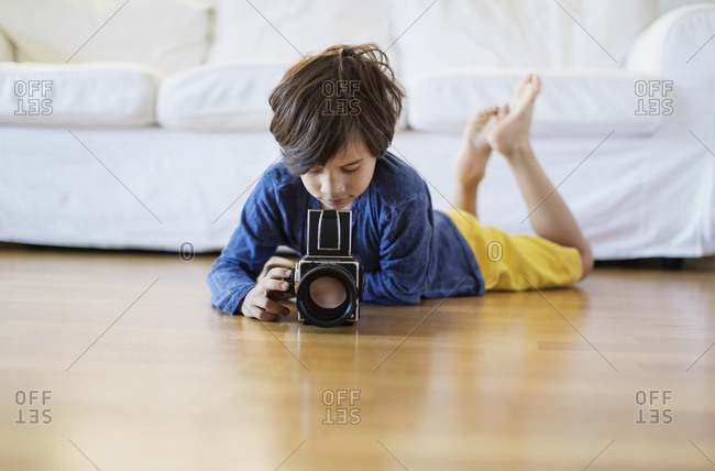 Boy lying on the floor at home using an old-fashioned film camera