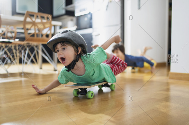 Toddler boy at home lying on skateboard wearing helmet having fun
