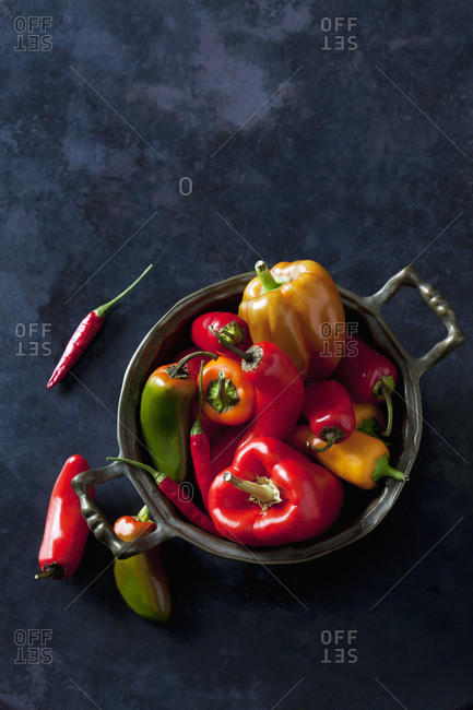 Bowl of various organic bell peppers and chili peppers on dark ground