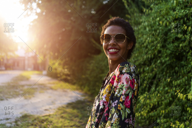 Portrait of happy young woman wearing sunglasses outdoors at sunset