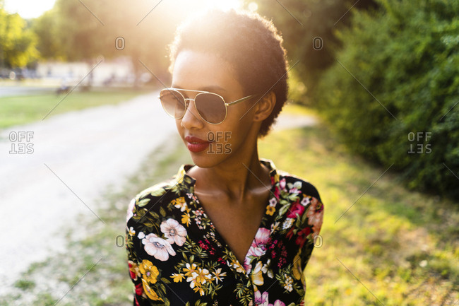 Fashionable young woman wearing sunglasses outdoors at sunset