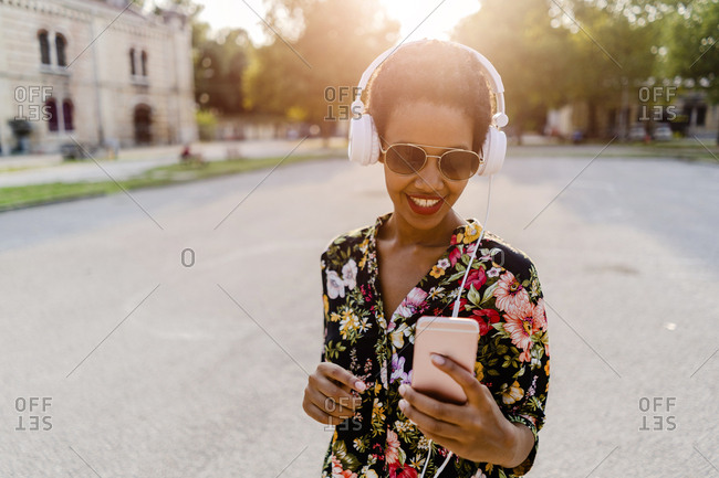 Happy fashionable young woman with headphones and smartphone outdoors at sunset