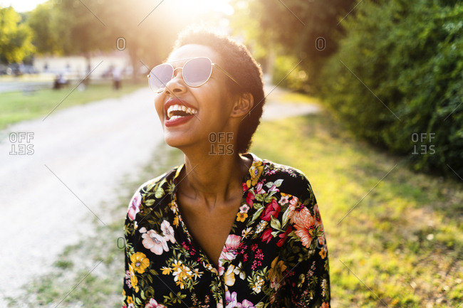Laughing young woman wearing sunglasses outdoors at sunset